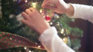 Closeup of the hands of a little girl putting Christmas ornament on the Christmas tree at home.