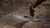 Close-up of trail runners shoe as he runs through a mud puddle in a forest. - Super Slow Motion - filmed at 240 fps