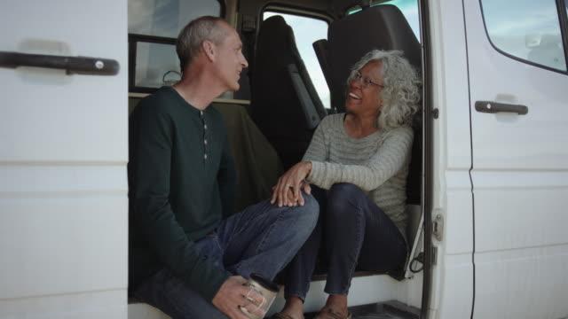 Closeup of Two Adventurous Seniors Chatting in Their Campervan