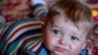 Close-up of unhappy baby looking at camera