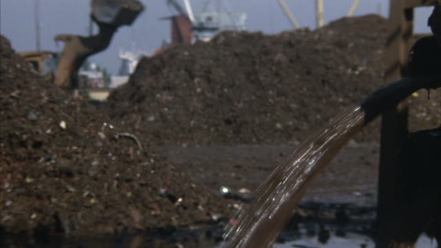 Close-up of wastewater flowing out of a pipe with a bulldozer and other heavy machinery working in the background.