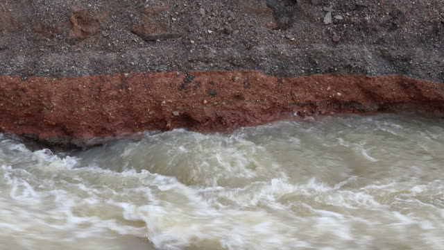 Close-up of water eroded under the road.