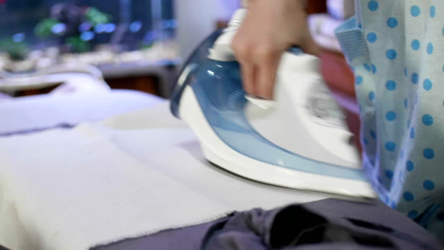 Close-up Of Woman Ironing Clothes With A Steaming Iron