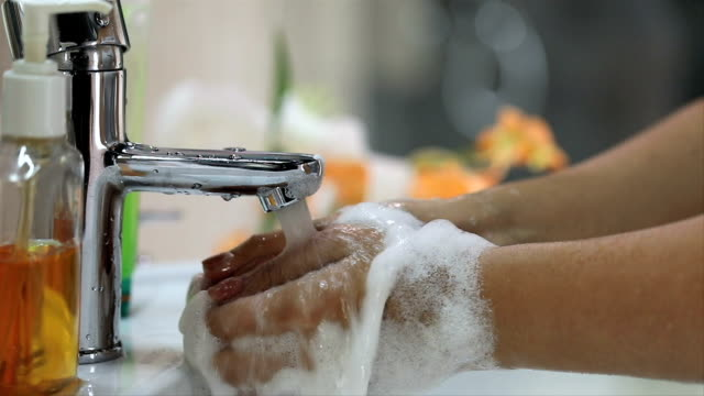 Close-up of woman washing her hands in bathroom, Delhi, India