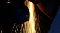 Close-up of worker cutting metal with grinder.