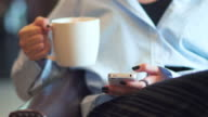 Close-up of young woman using smartphone in coffee shop