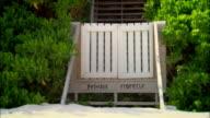 Close-up pan Fence reading Private Property near bush on beach/ Harbor Island, Bahamas
