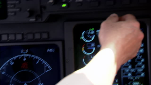 Close-up pan Pilot navigating control panel in cockpit of private airplane
