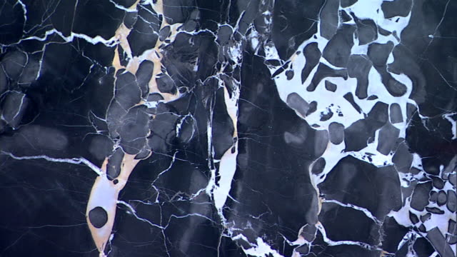 Close-up pan right across black and white marble.