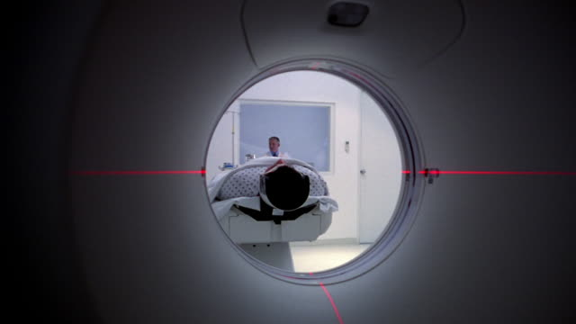 Close-up Patient entering CAT scan machine as red lasers surround him/ Panama City, Panama