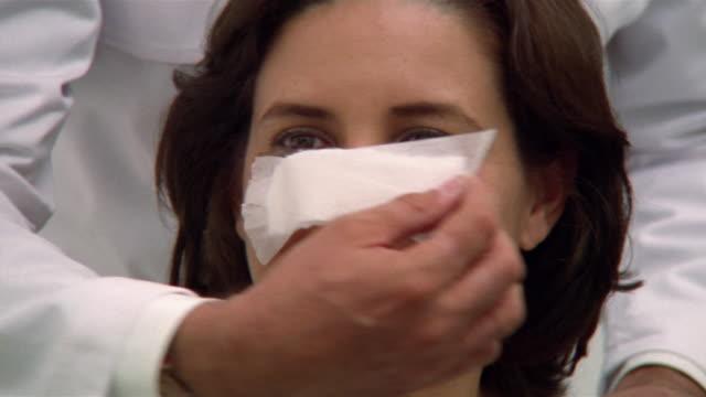 Close-up Plastic surgeon removing bandage from woman's nose after surgery/ Panama City, Panama