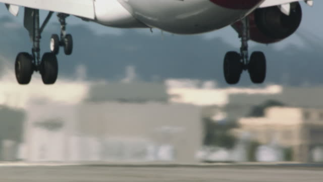 Close-up pn landing gear entering frame as Virgin America jet passenger plane touches down for rough landing