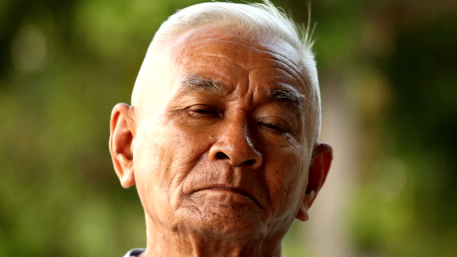 close-up portrait of a asian senior man thinking about something