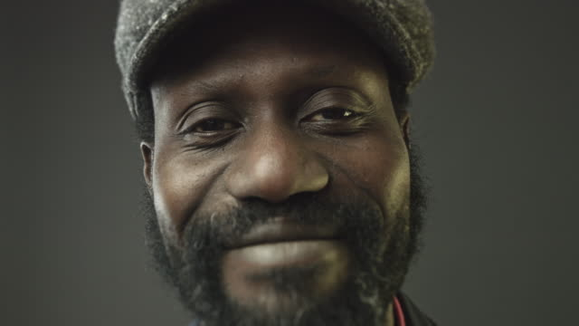 Close-up portrait video of happy well dressed african man looking at camera