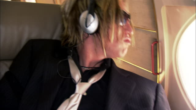 Close-up Rock star listening to headphones and head banging on private airplane
