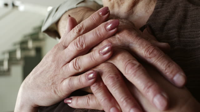 Close-up, senior couple hugging at home