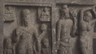 Close-up sequence showing relief carvings in the smoke-filled chaitya of the Karla Caves in Maharashtra, India.