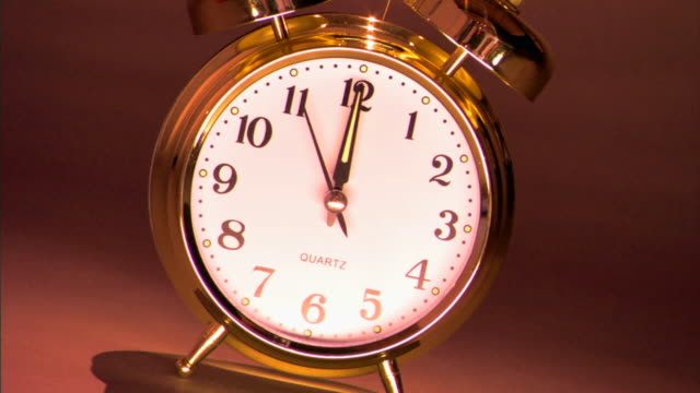 Close-up shot of a brass alarm clock at 12:00.