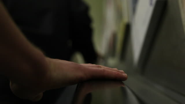 Close-up shot of a hand of a person travelling up an escalator at a tube station, London, UK.
