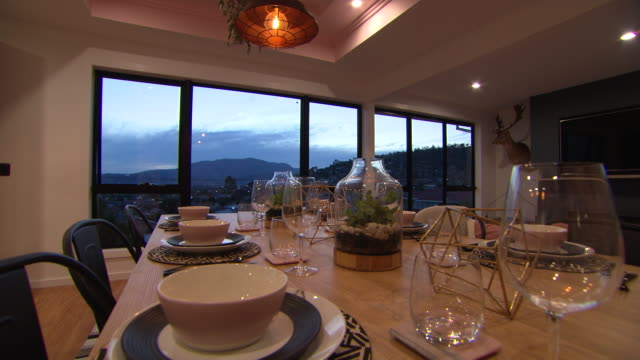 Closeup shot of a table setting in a restaurant with timelapse day to night view through the window starting with sun setting behind the mountains...