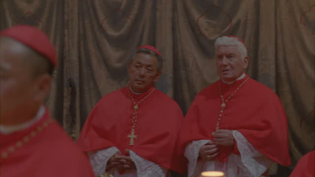 Close-up shot of Catholic cardinals gathered in a meeting.