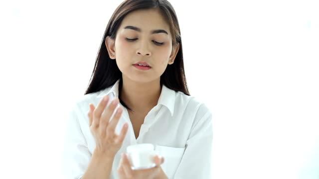 Closeup shot of hands applying moisturizer. Beauty woman holding a glass jar of skin cream. Shallow depth of field with focus on moisturizer