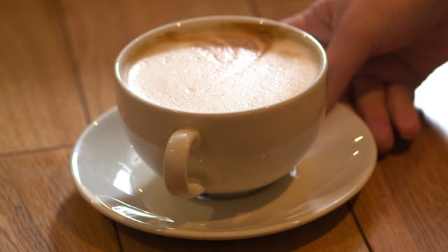 Close-up shot of hands putting down and picking up a coffee cup from a wooden table, UK.