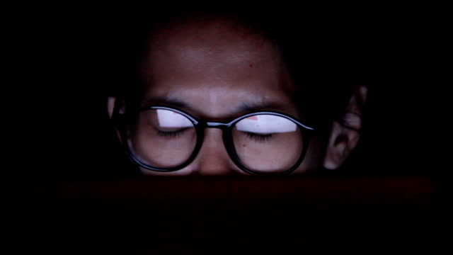 Closeup shot of woman in glasses surfing internet at night:1920x1080 FULL HD