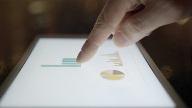 Close-Up Shot on Human Hand Using a Digital Tablet. Business Figures and Statistics as Symbol for Profit on the Screen.