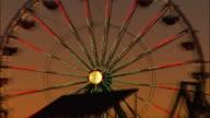 Close-up. Silhouette of illuminated ferris wheel at Santa Monica Pier.