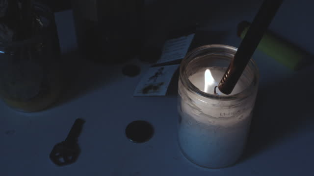 A closeup, slow motion shot of a candle being lit at night - 4k