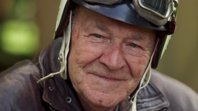 Close-up Smiling senior man wearing motorcycle helmet and motorcycle goggles / Washington, USA