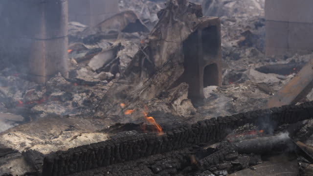 Close-up smoldering rubble of a burned structure