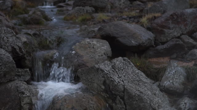 Close-up, static shot of smoke billowing over a stream as it falls over rugged stones in South Iceland.