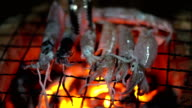 close-up: tiny fresh squid on coal fire to make roast squid