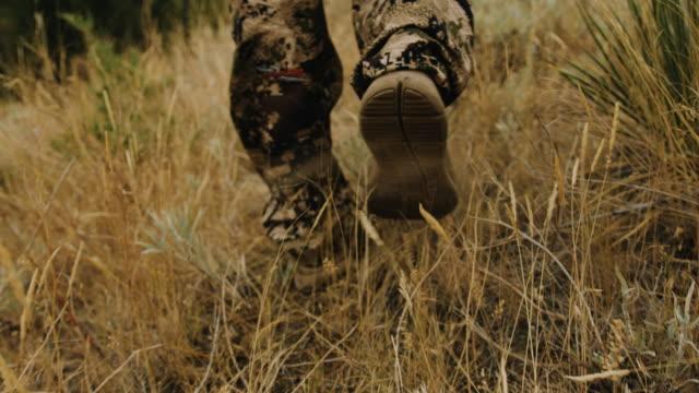 Closeup Schuss eines Jägers Füße zu verfolgen, wie er durch das Wildgras geht.