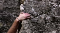 Closeup tracking shot of a man's hands trying to find a solid grip while rock-climbing.