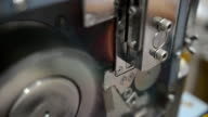 close-up: using grinder to cut plastic extrude to form plastic pellet