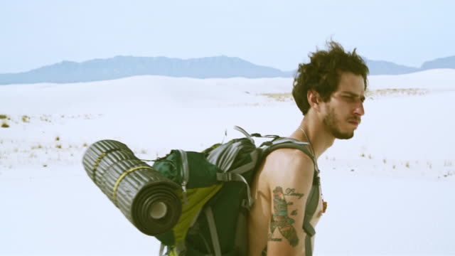 Closeup video of the young tattooed Caucasian man, tourist - hiker with the big backpack, walking through the sandy desert. White Sands National Monument, New Mexico, USA.
