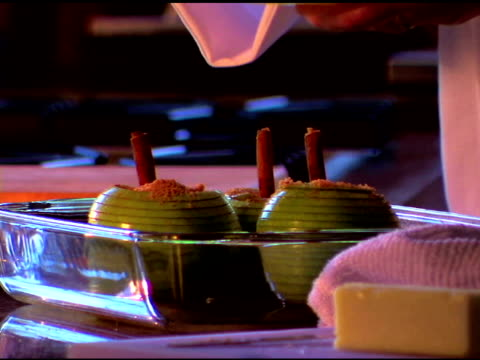 Close-up view of a chef¿s hands as she spoons liquid on apples she is preparing for dessert.