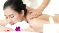Closeup view of a young woman with oiled skin having thai massage of her back and shoulders in spa.