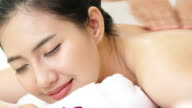 Closeup view of a young woman with oiled skin having thai massage of her back and shoulders in spa club.