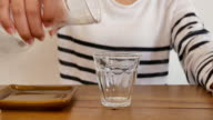 Closeup woman pouring water into glass from water filter pitcher for drink