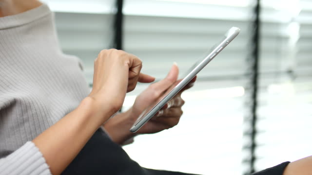 Close-up young woman using tablet