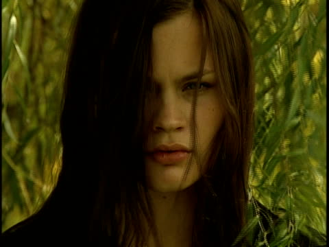 Close-up Young woman with long brown hair staring behind willow tree branches and leaves