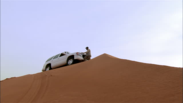 Close-up zoom in man using laptop computer on hood of SUV on sand dune in desert