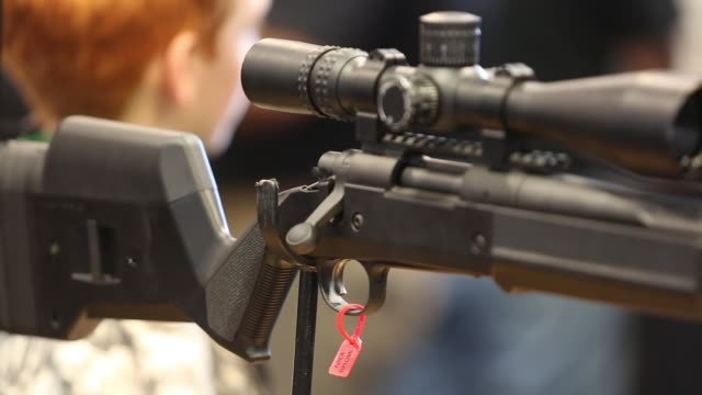 Closeups of a sniper rifle at National Rifle Association Annual Meeting Show