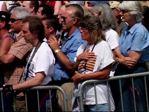 Closing Ceremony at Ground Zero May 30 2002 CU spectators including woman wearing American flag Tshirt holding hand over heart Audio Taps played on...