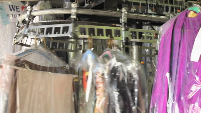 MS PAN TU Clothes moving around on mechanical rack in dry cleaners  / Richmond, Virginia, USA.