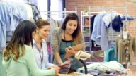 Clothing store employees work together on inventory
